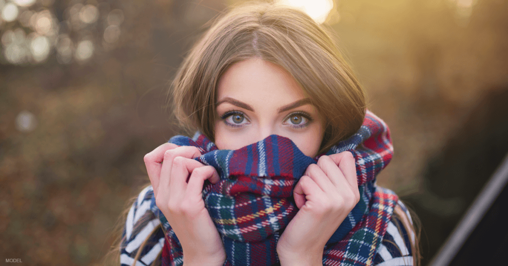 A woman covers her face with a scarf.
