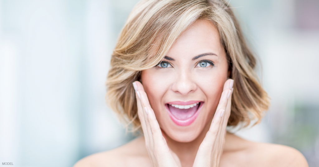 Woman is excited about the results of her cheek filler.