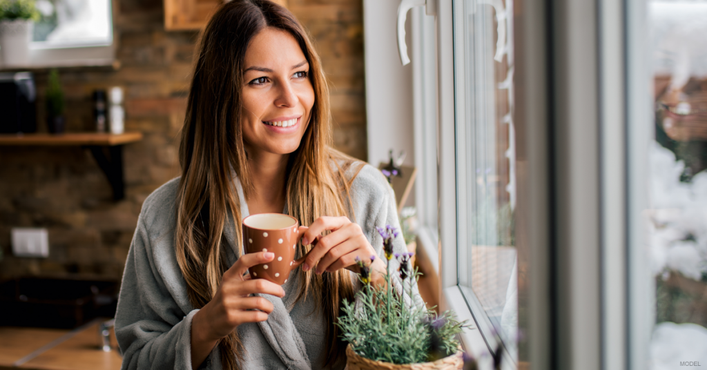 Woman looks rejuvenated and drinks her coffee.